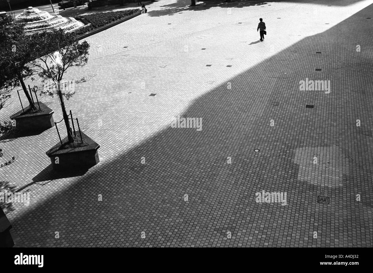 A man walking across an empty space. Hong Kong, Peoples' Republic of China, HKSAR - Stock Image