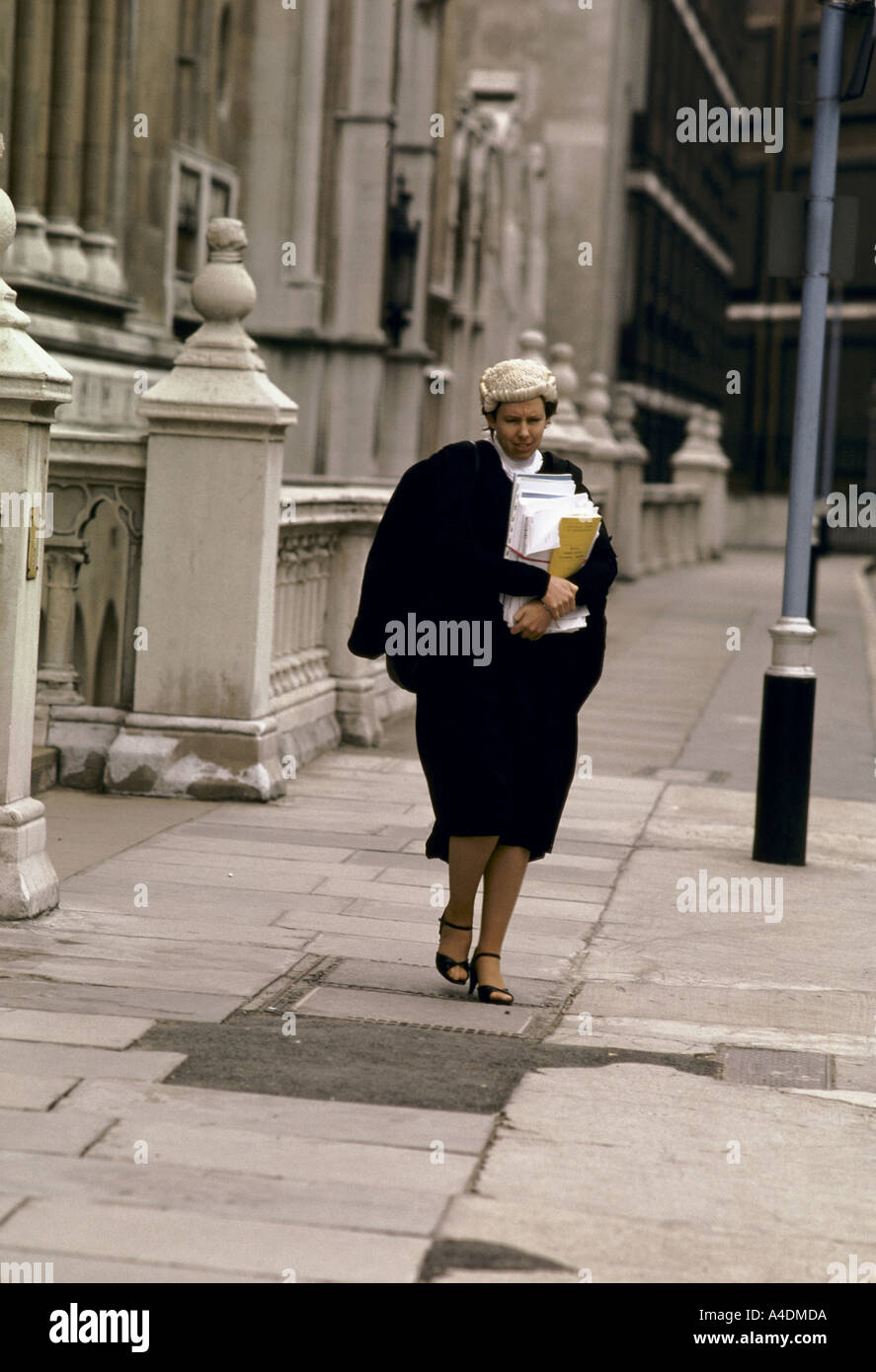 A female barrister wearing a wig & gown walking outside the High ...