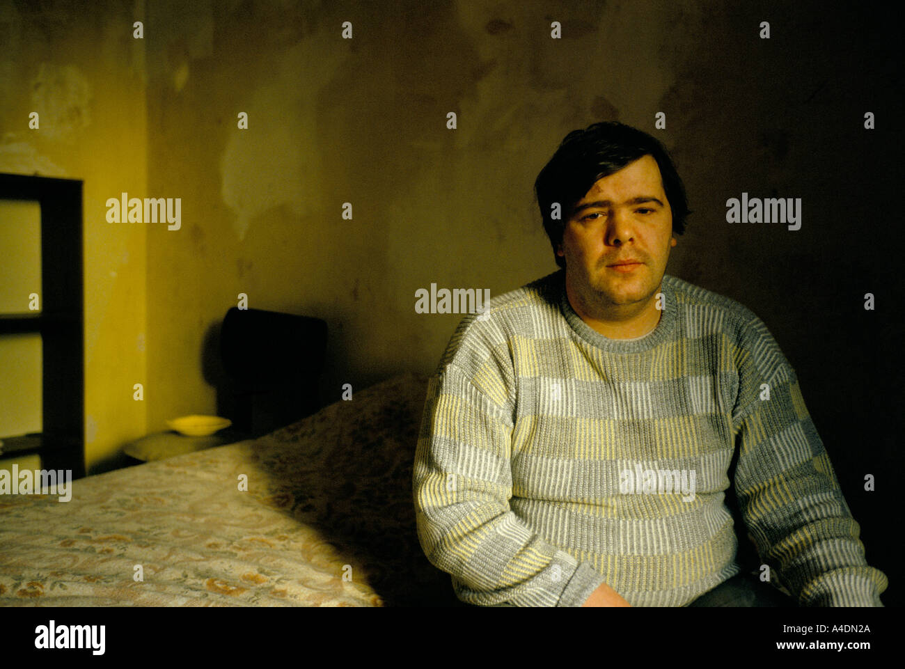 A man in poor housing, Glasgow, Scotland - Stock Image