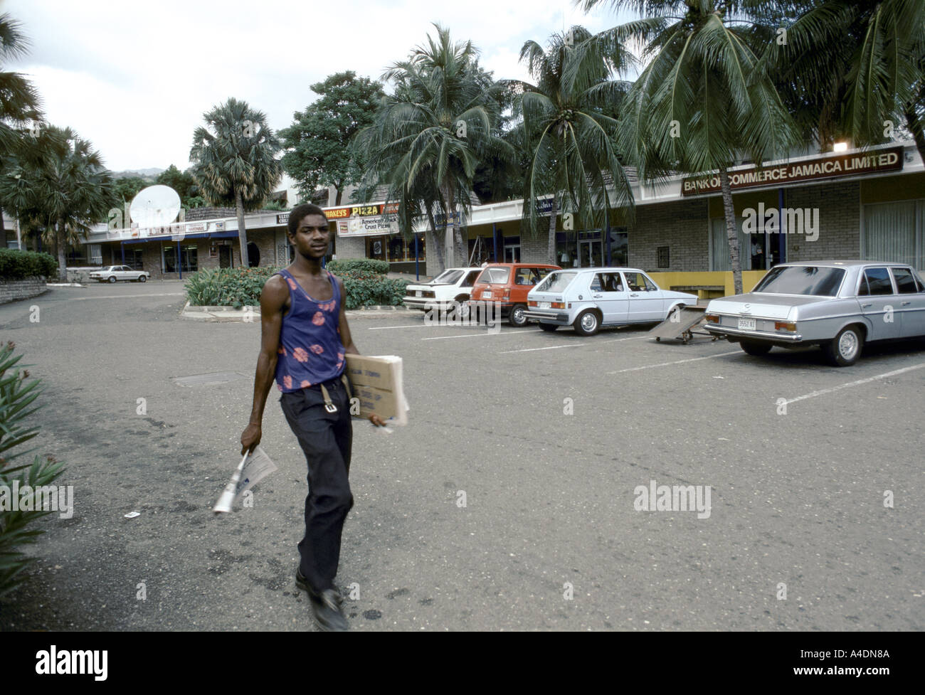 A young man walking past a quiet tree-lined street with parked cars and shops, Kingston, Jamaica, - Stock Image