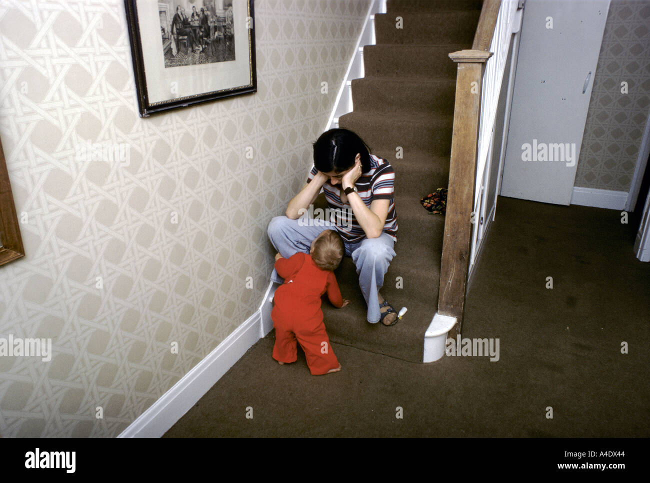 Woman suffering from depression sitting on a step at the bottom of the stairs with child looking at her - Stock Image