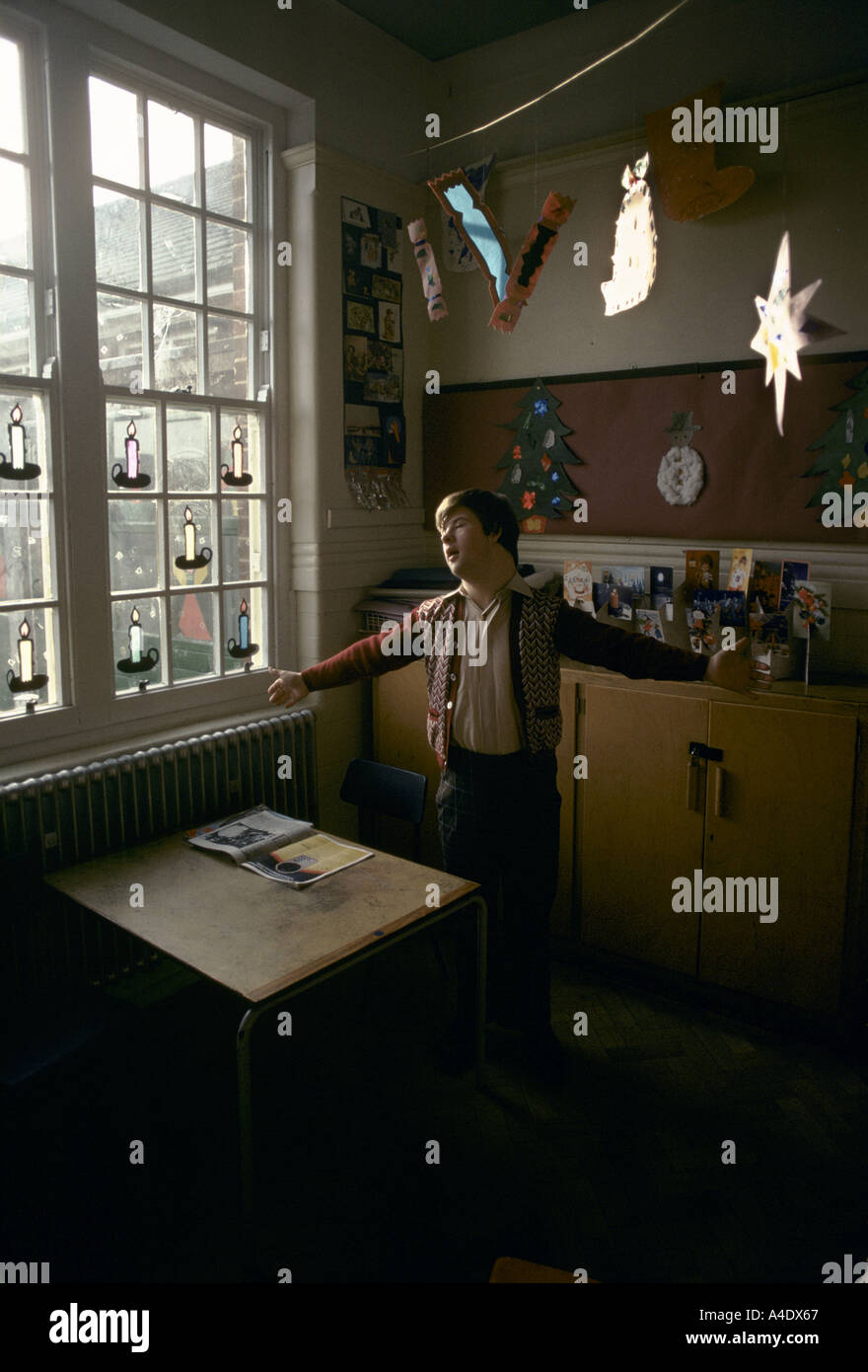 Mentally handicapped child in a home with christmas decorations in the window - Stock Image