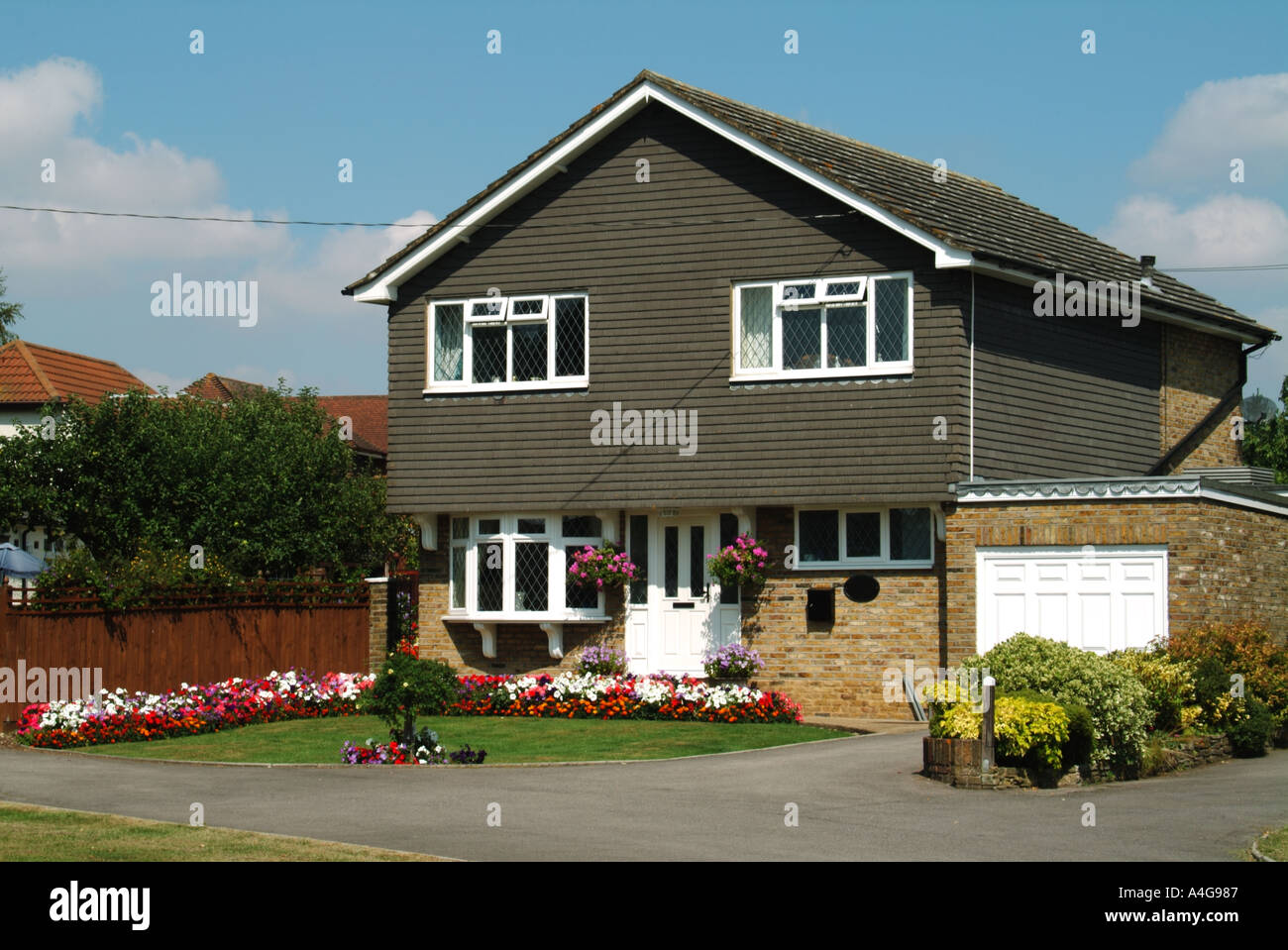Detached house with garage and front open plan garden drive elevation clad with vertical tile hanging - Stock Image