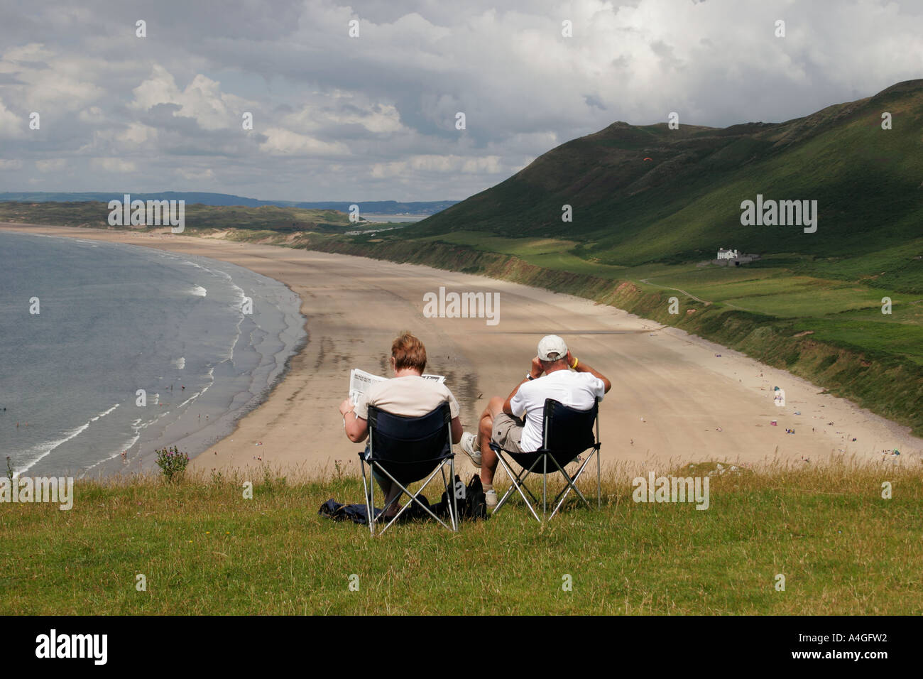 COUPLE IN DECKCHAIRS, OVERLOOKING RHOSSILI BEACH, GOWER PENINSULA, SOUTH WALES, U.K. - Stock Image