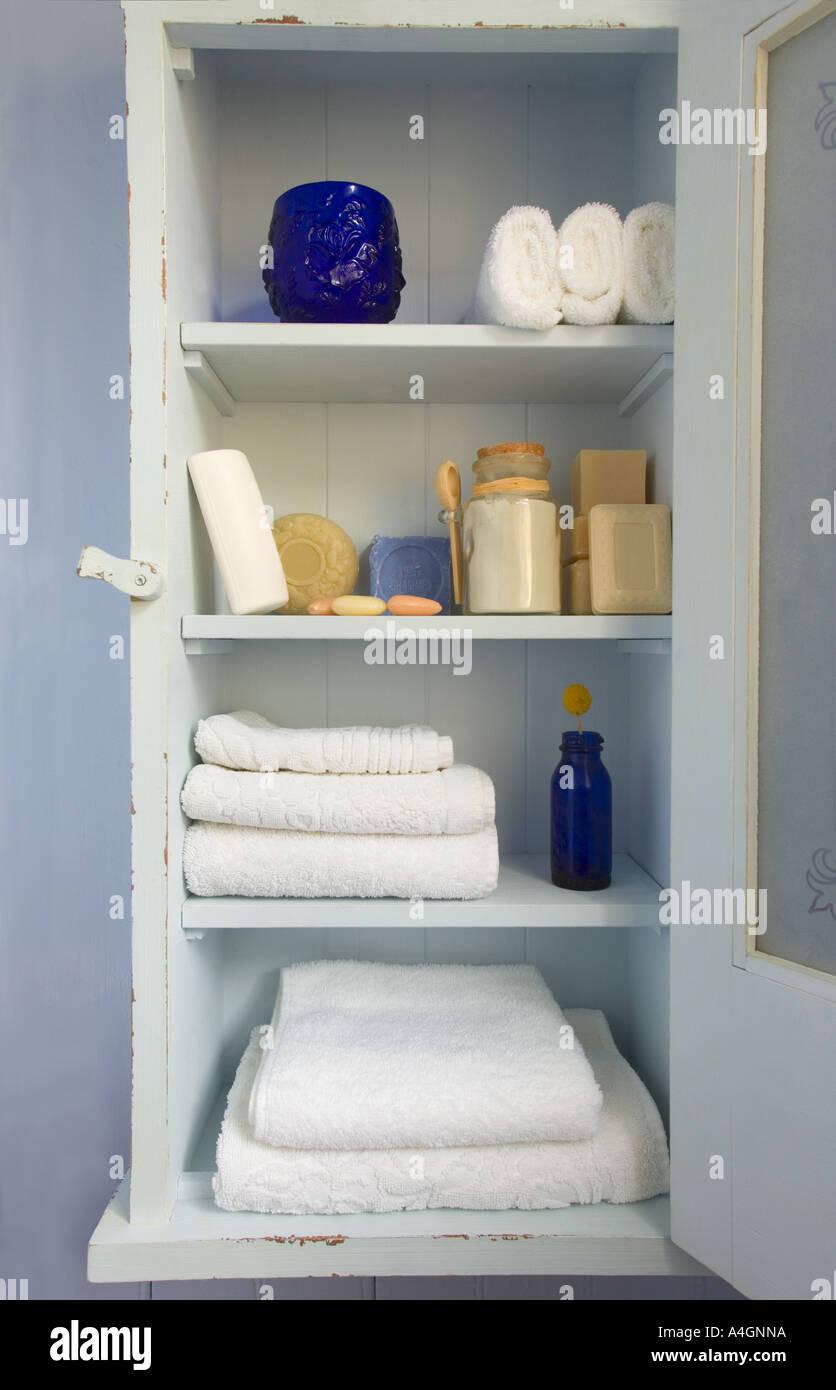 Vintage Bathroom Cabinet With Towels, Soaps And Blue Bottle.