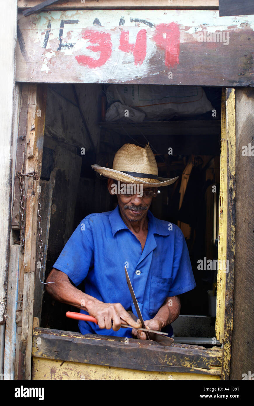 Man with hat sharpening a scissor in a favela, Sao Paulo, Brazil - Stock Image