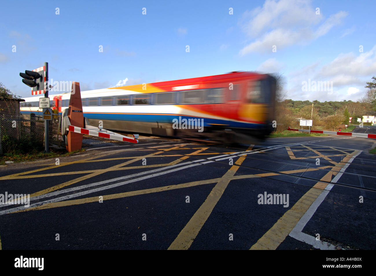 """Level crossing"" train crossing a level crossing, Britain UK - Stock Image"