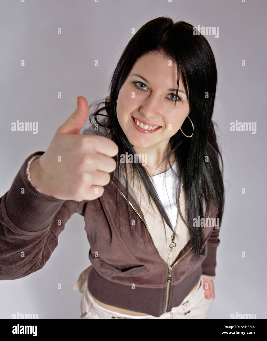 Young woman aged 16 with black hair gives the thumbs up - Stock Image