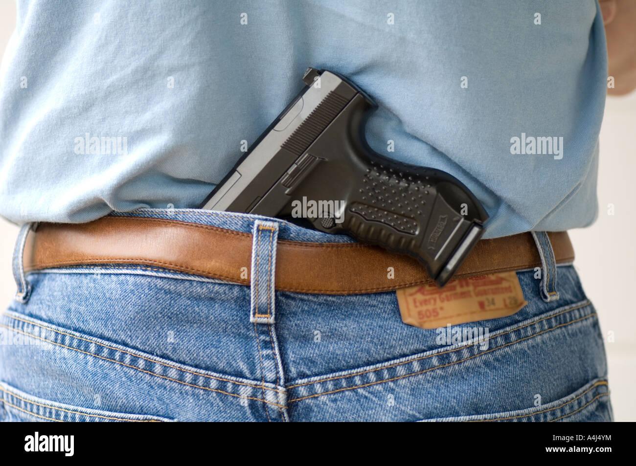 handgun stuck in jeans pocket - Stock Image