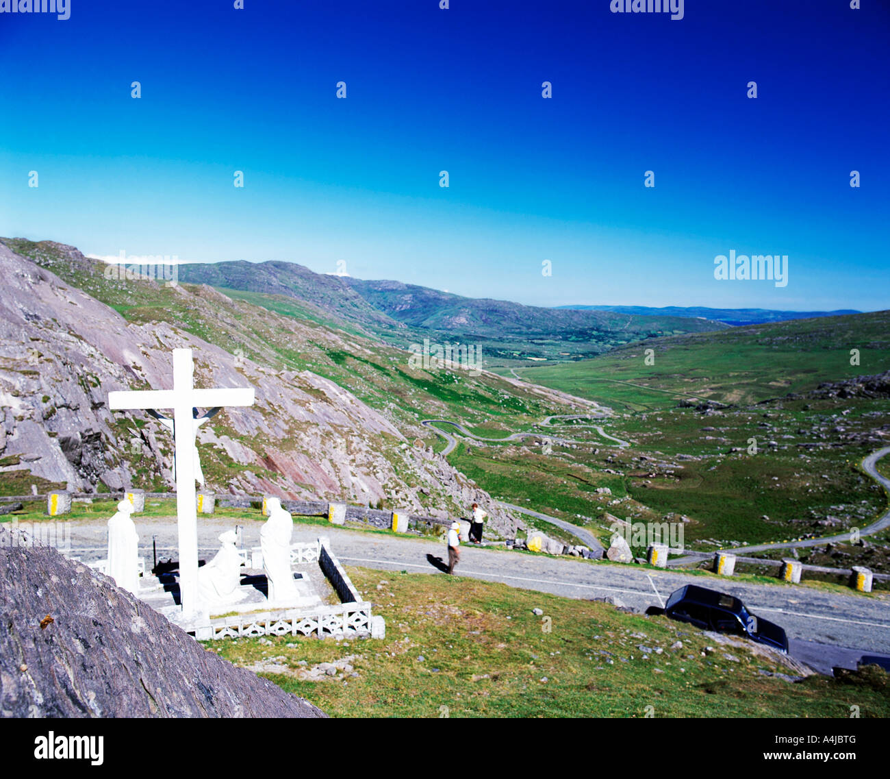 tall religious crucifix stands on top of mountain looking down on the valley below Stock Photo