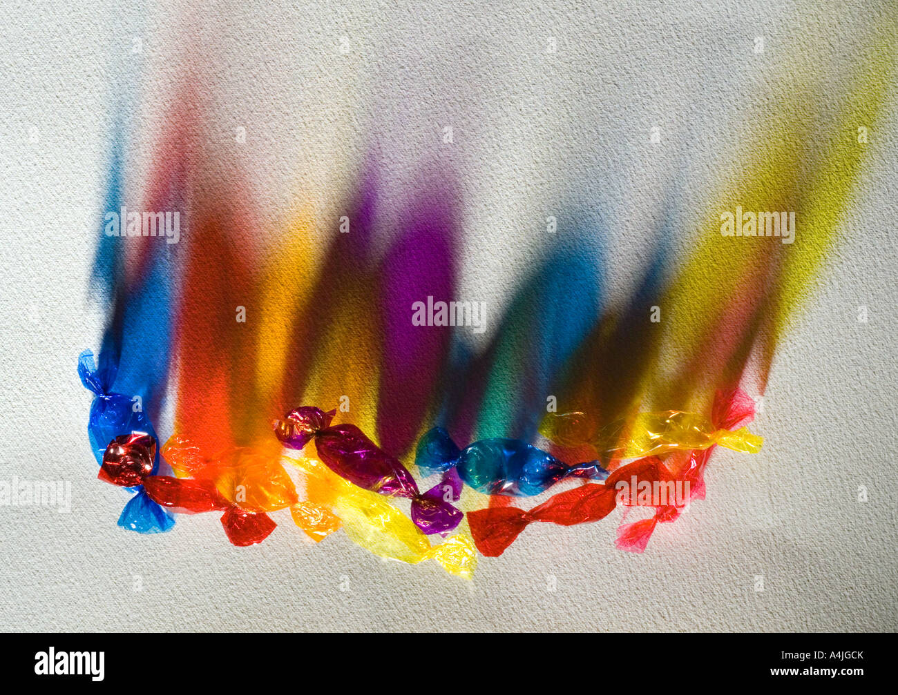 cellophane sweet wrappers with light shining through on textured paper - Stock Image