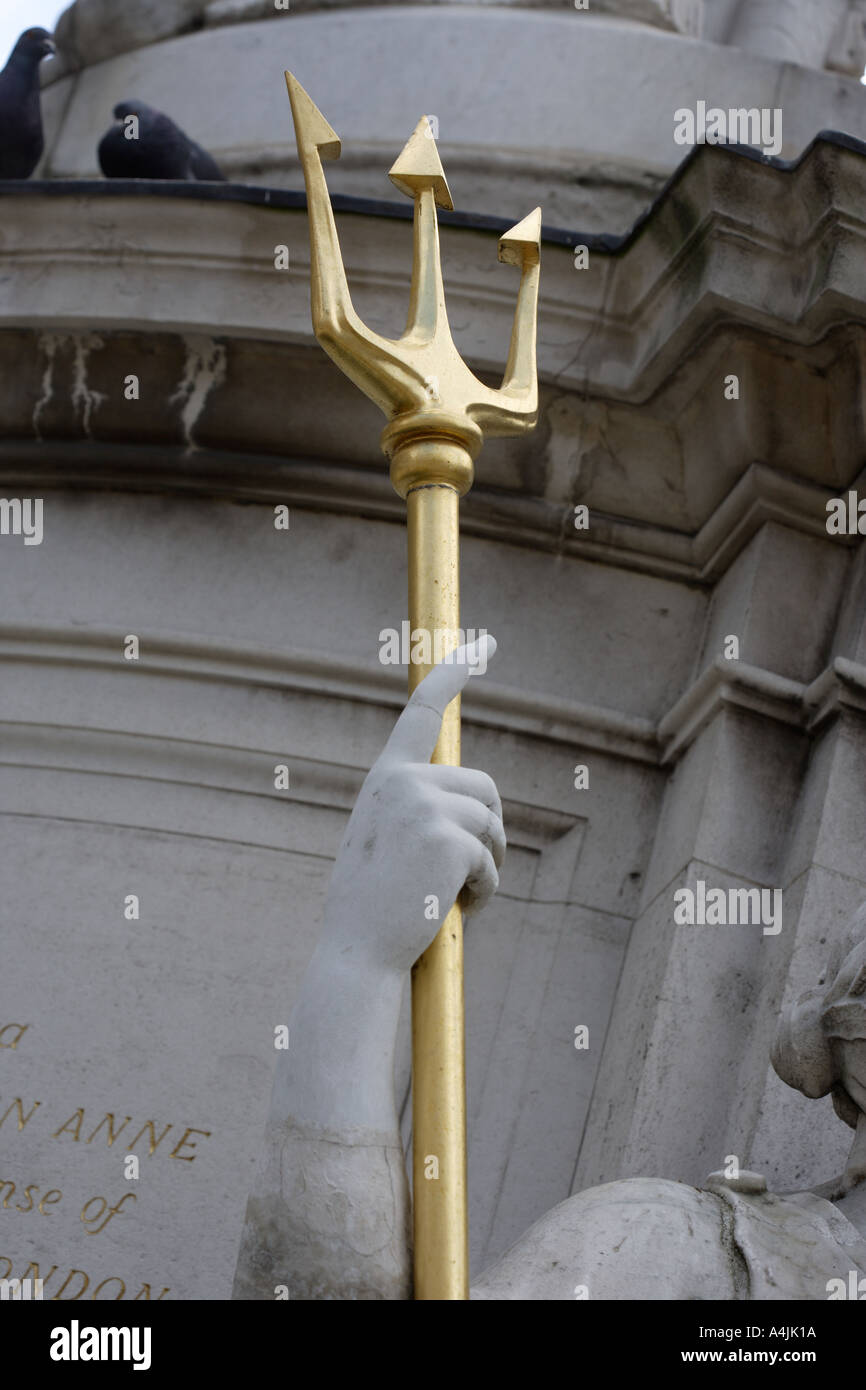 golden trident held by arm of statue - Stock Image