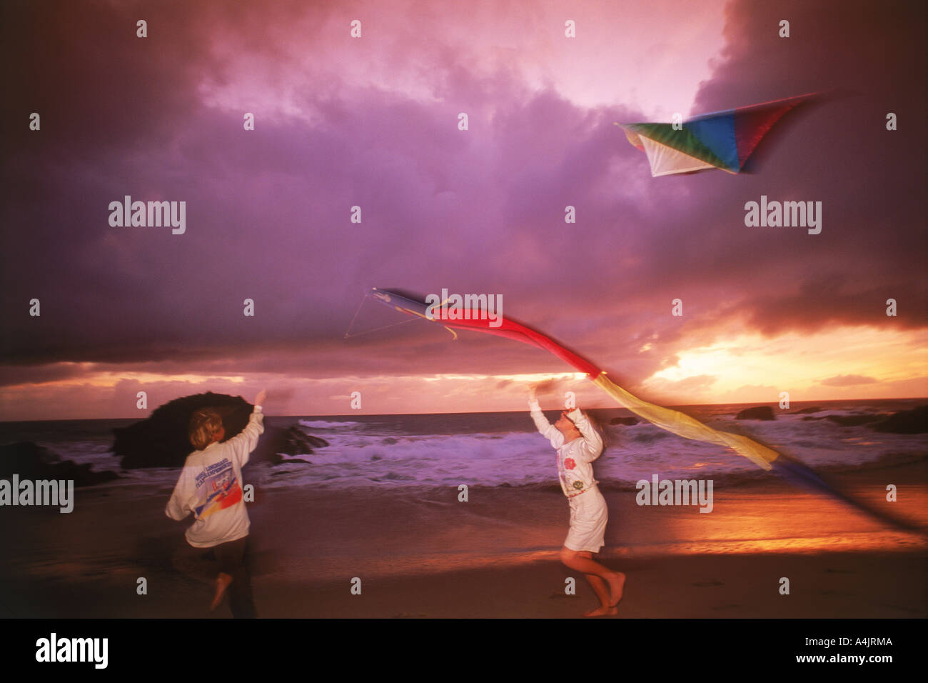 Kids flying kites on windy shore at sunset - Stock Image