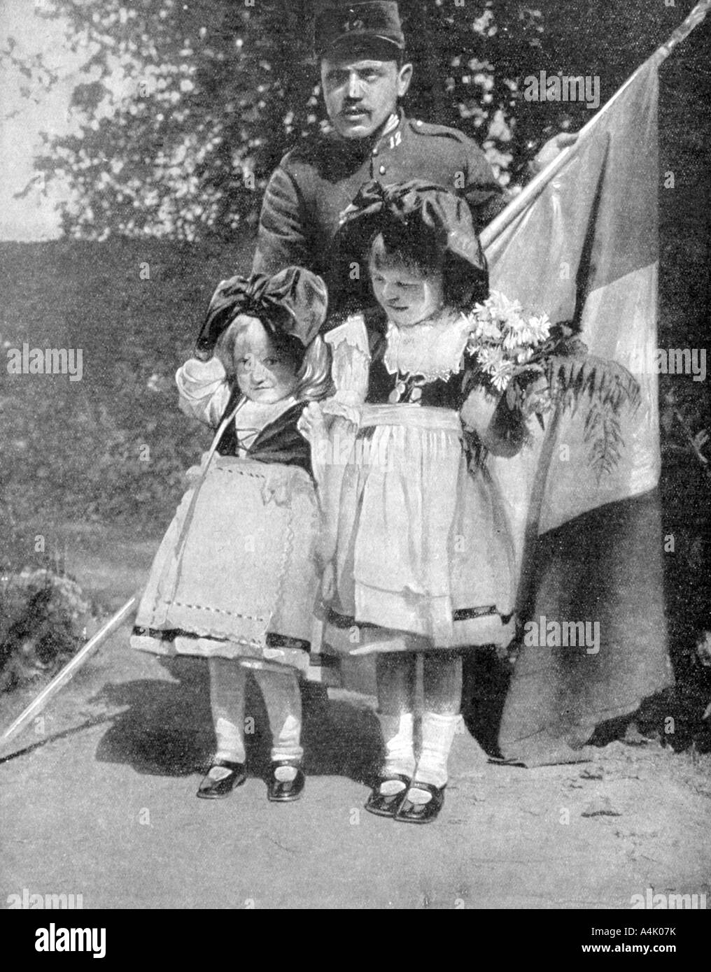 Young Alsatian children in traditional dress with a French soldier World  War I 1915 - Stock