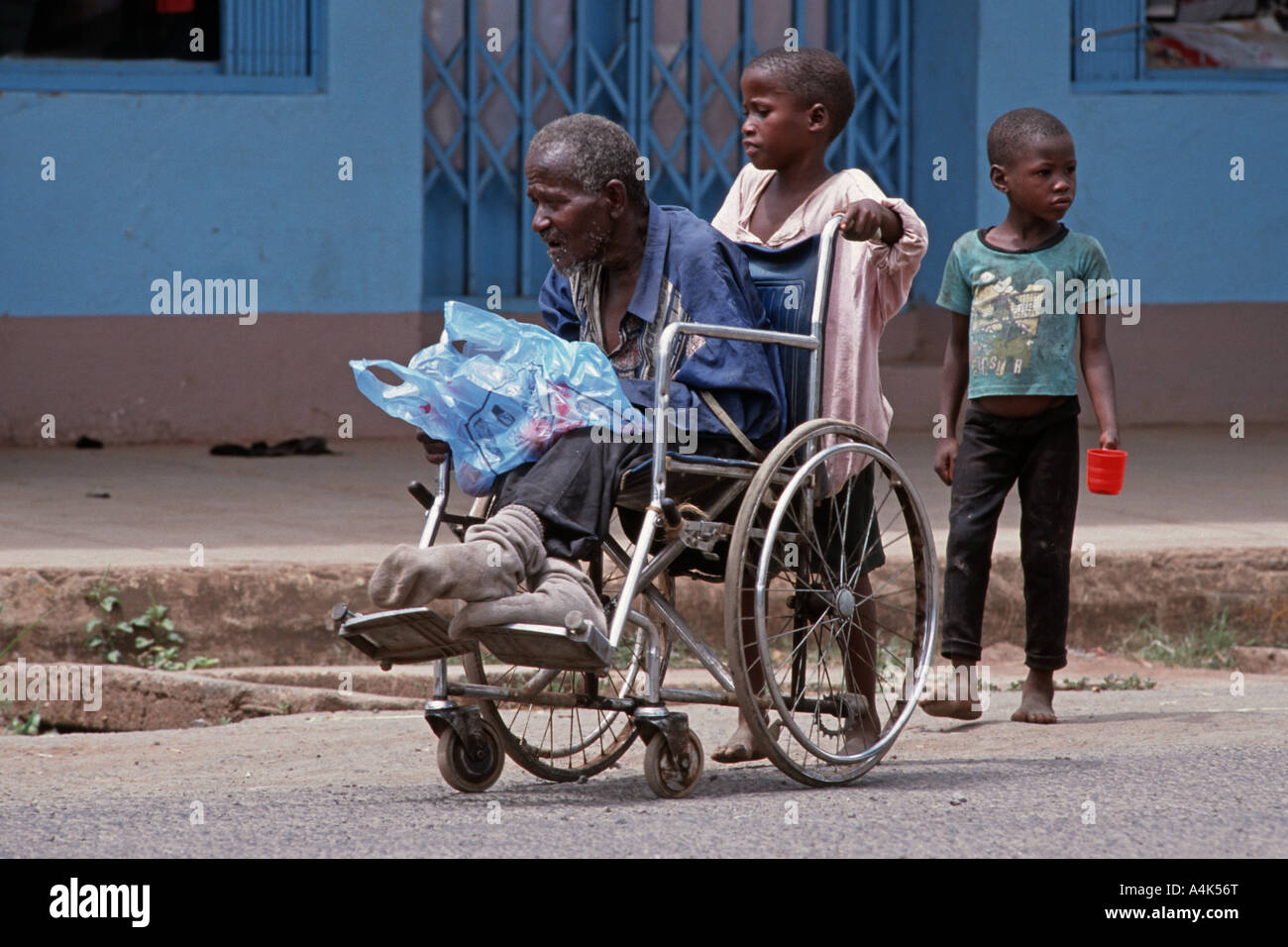 Children pushing a wheelchair with a handicapped relative to beg in the streets of Moshi, Tanzania - Stock Image