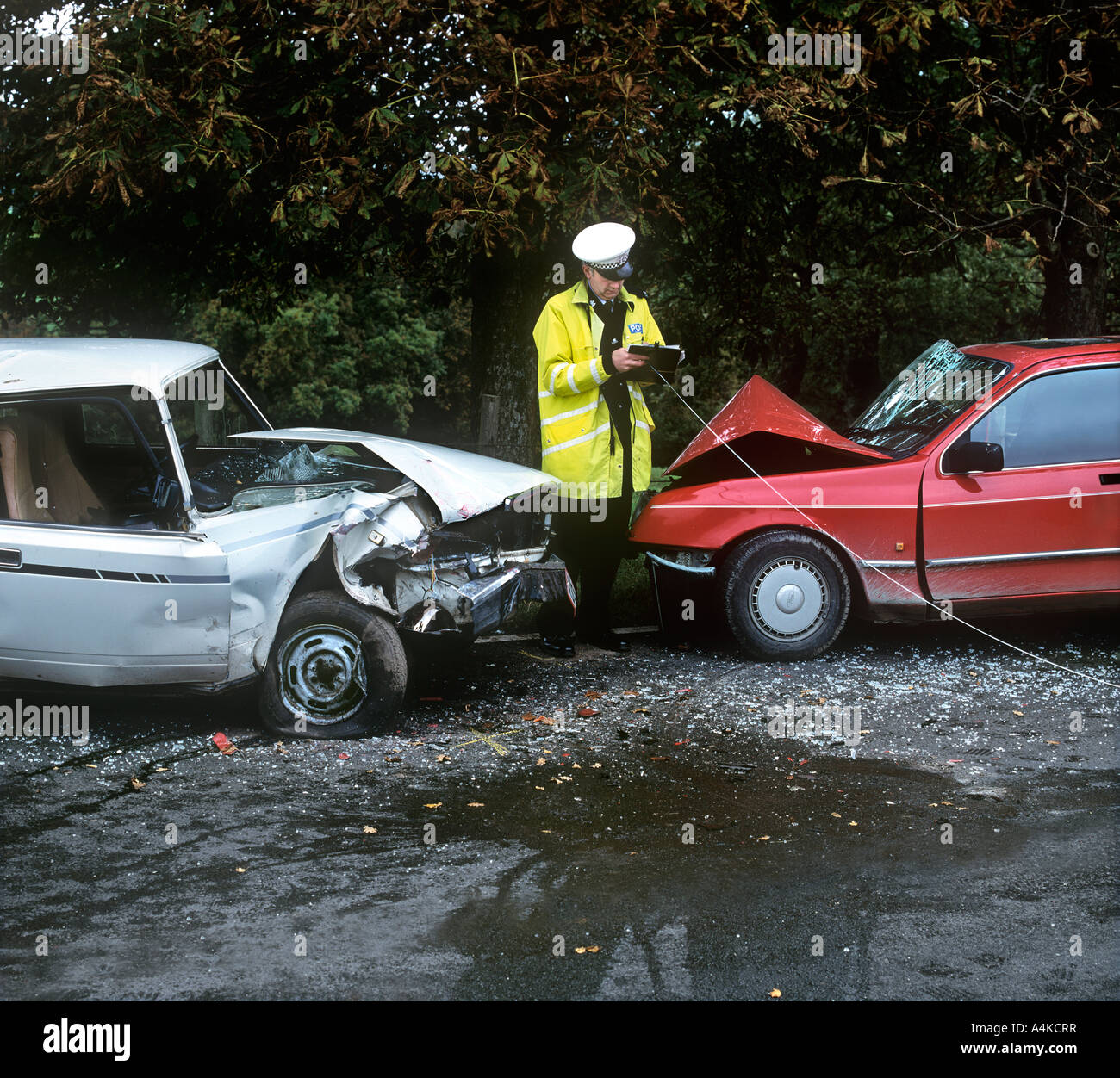 A policement taking measurements at the scene of a road accident. Stock Photo