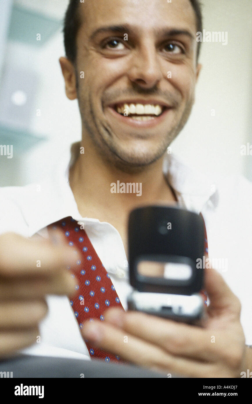 Man using cell phone, smiling - Stock Image