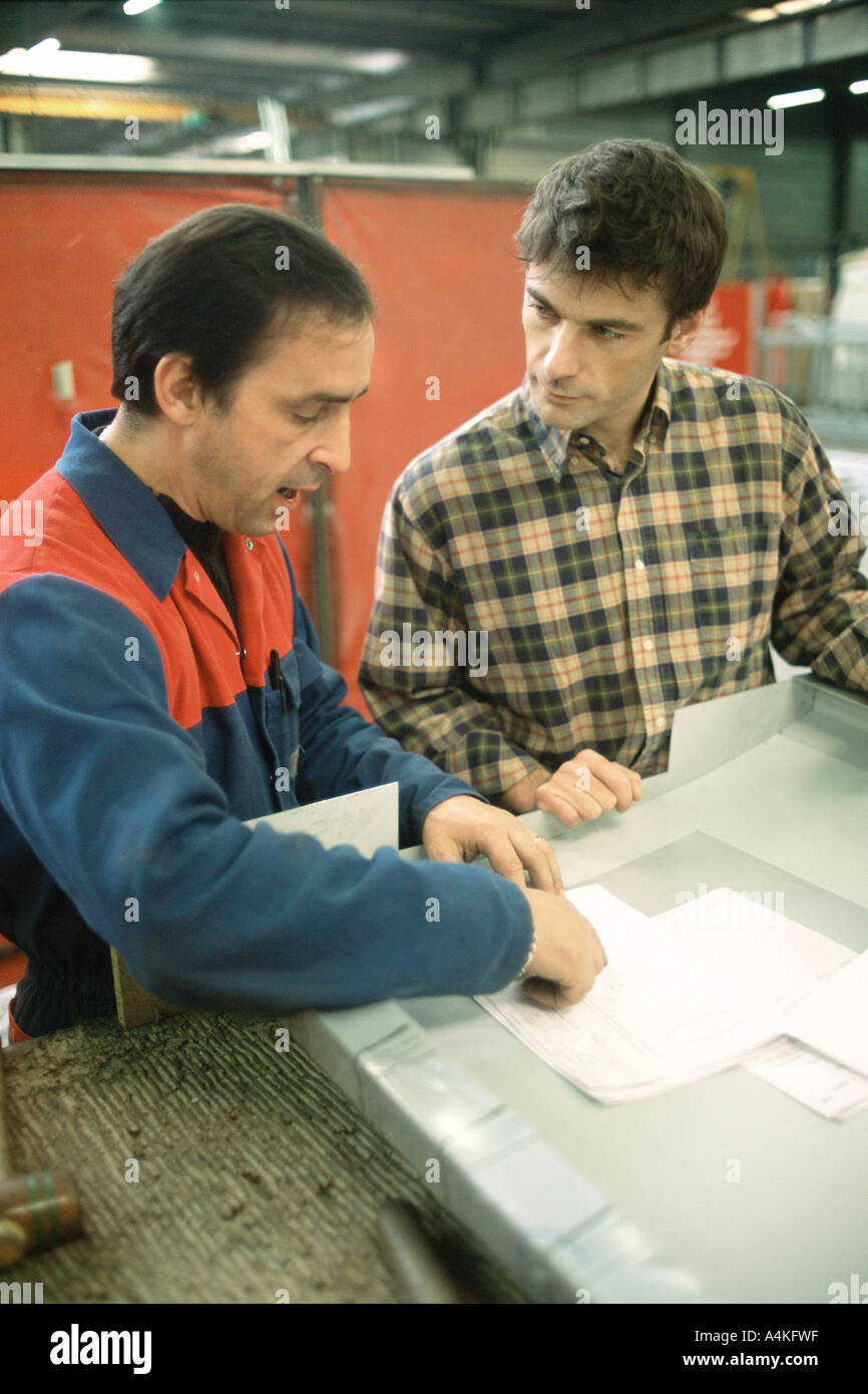 Manual worker and apprentice at work table - Stock Image