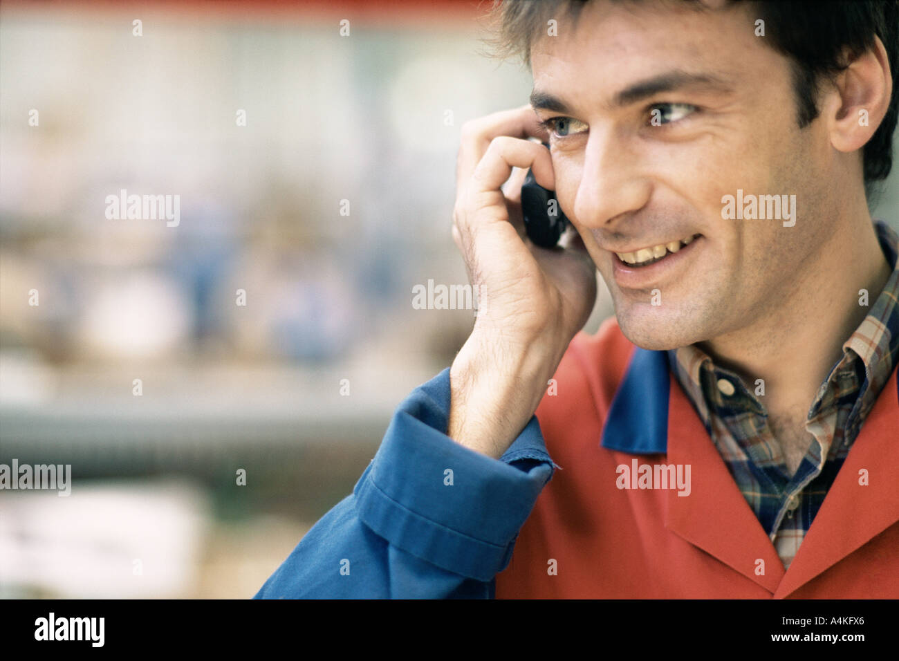 Manual worker using cell phone - Stock Image