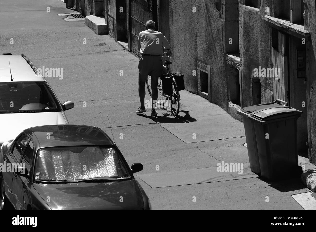 Old man walking with bike on sidewalk, rear view - Stock Image