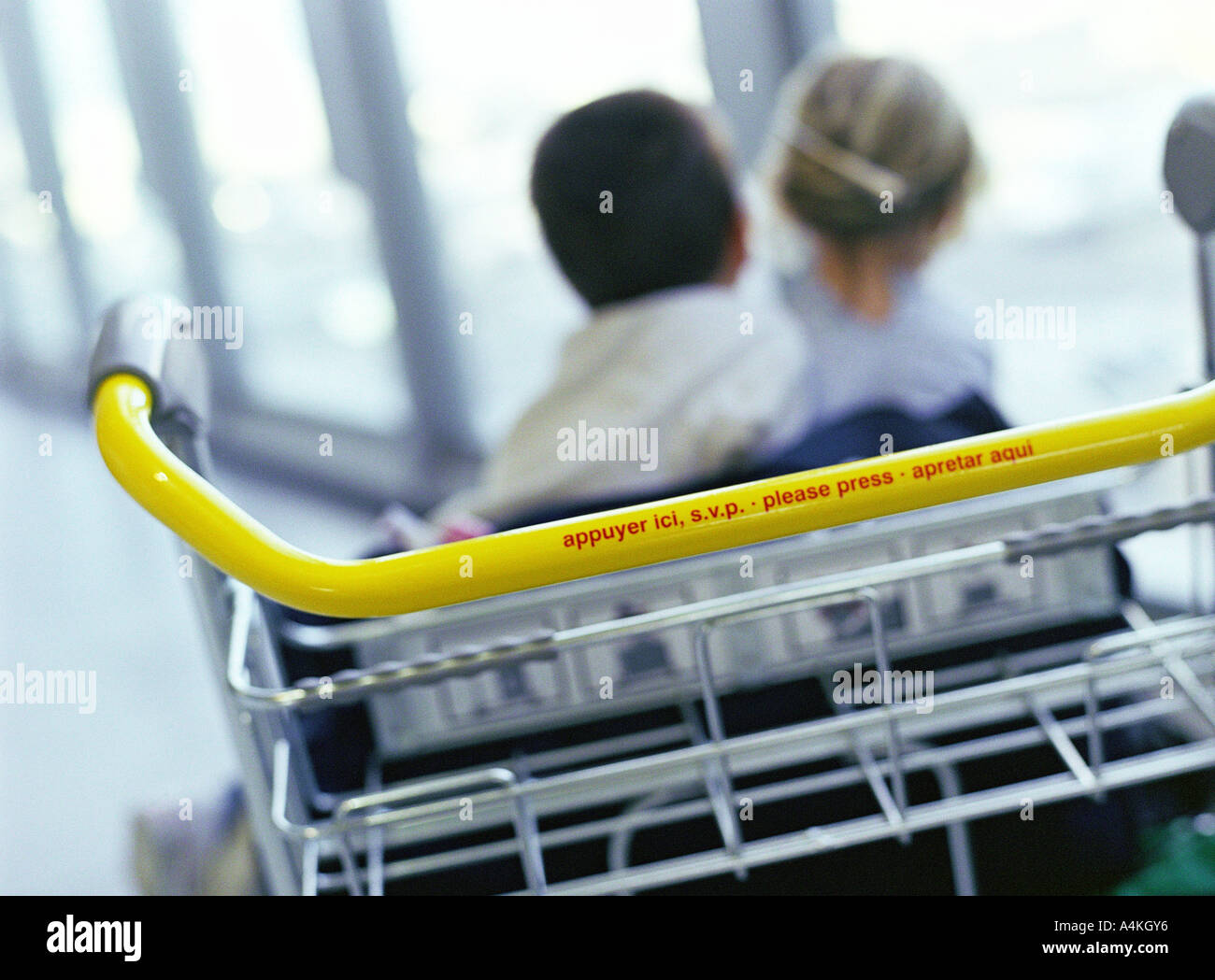 Boy and girl sitting on end of luggage rack, rear view Stock Photo