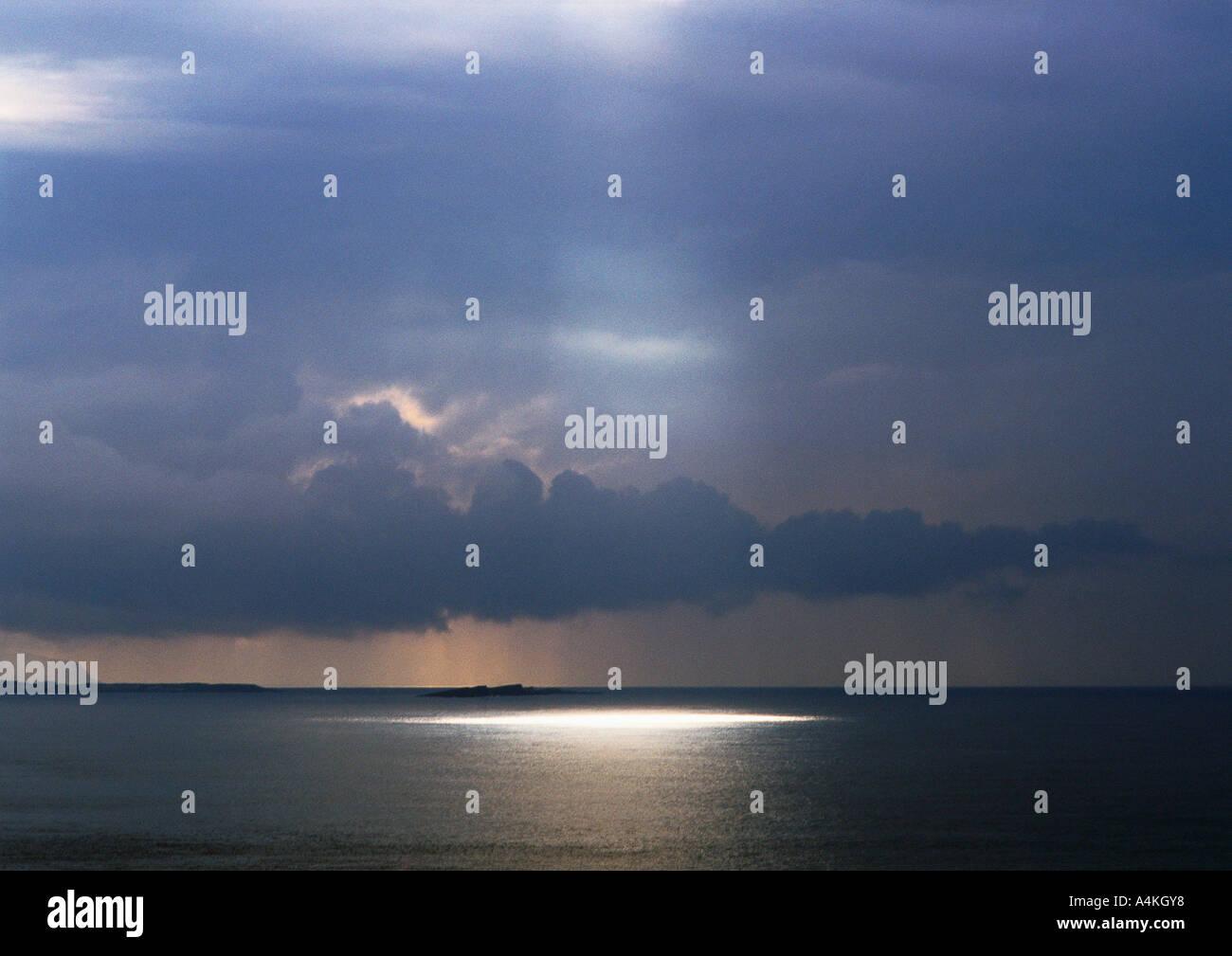 Sunbeam shining on sea - Stock Image