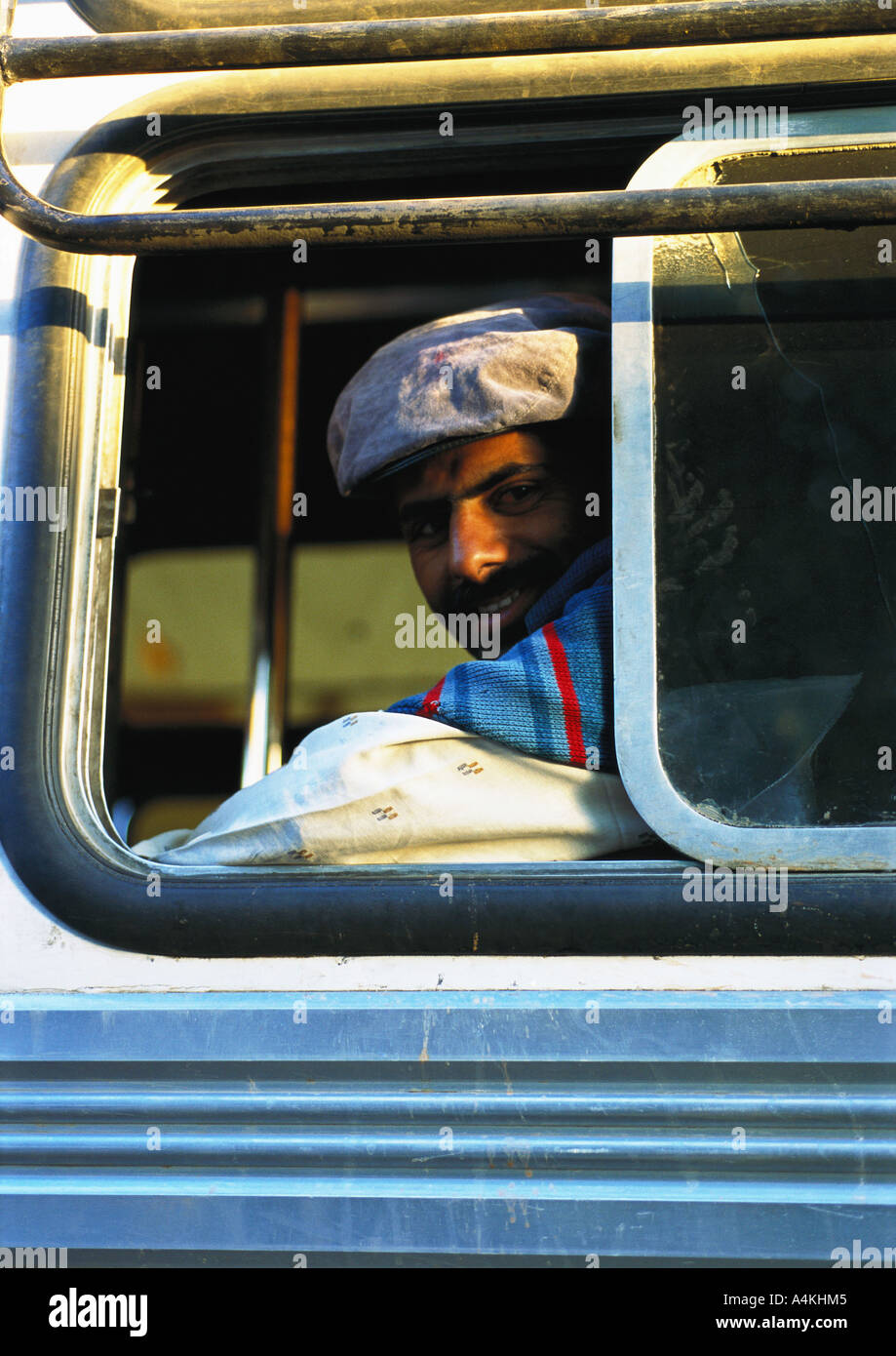 India, man looking out of bus window - Stock Image