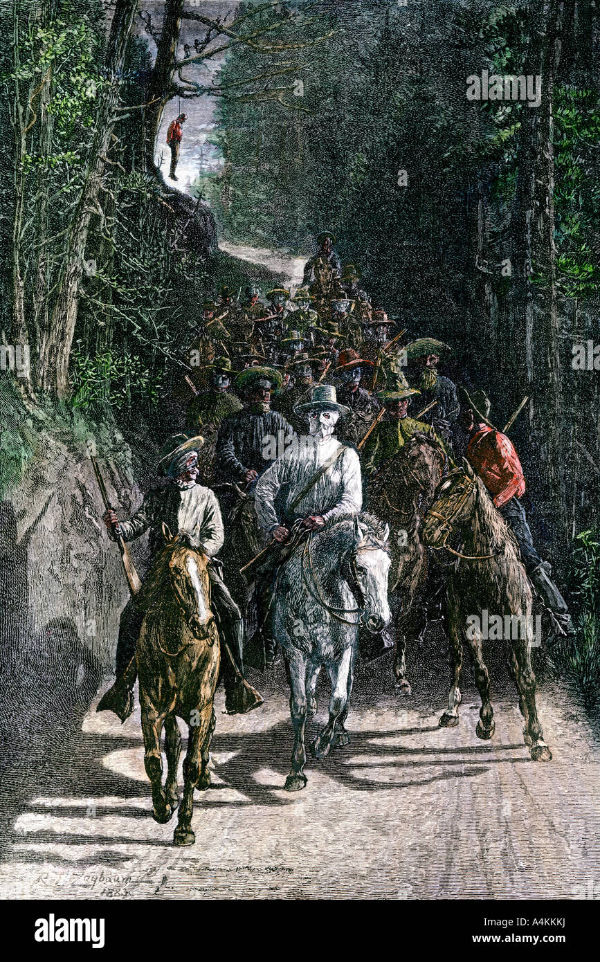 Mob of night riders carrying out a lynching 1800s. Hand-colored woodcut - Stock Image