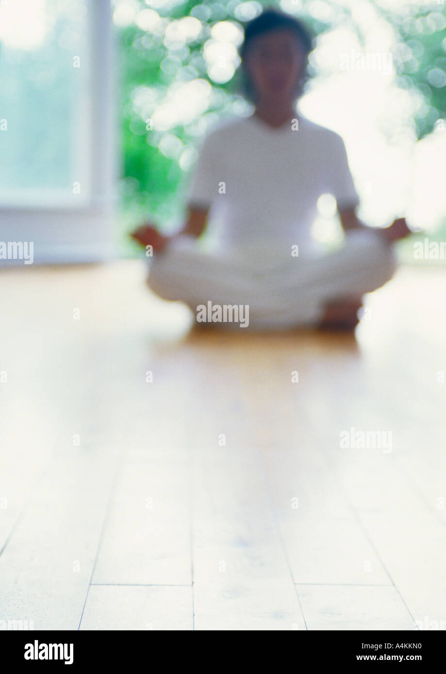 Person meditating in lotus position on floor, blurred - Stock Image