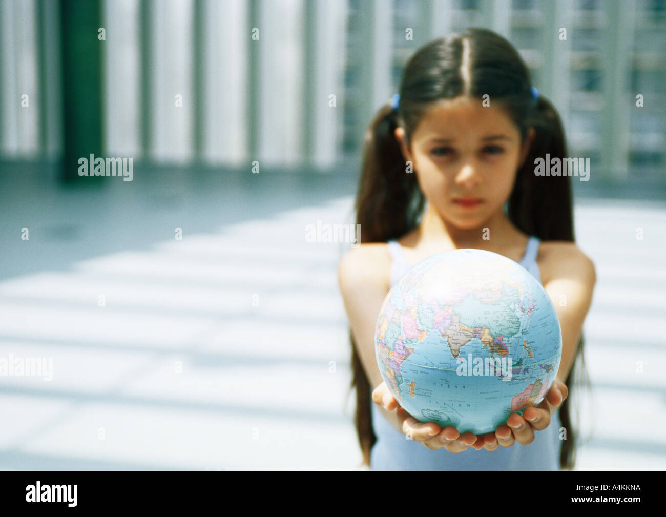 Girl holding out globe - Stock Image