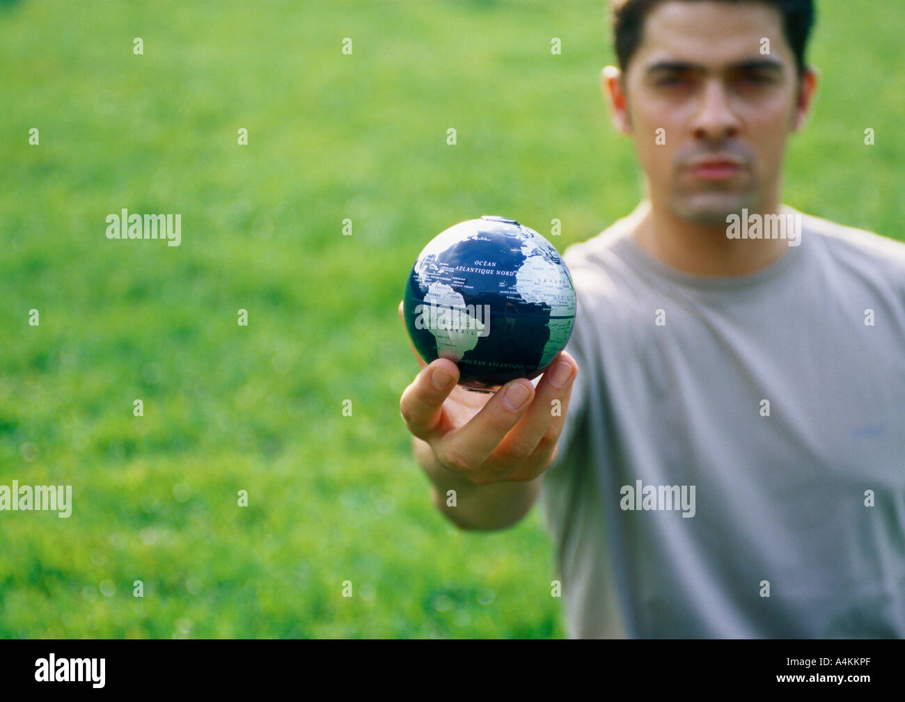 Man holding out small globe - Stock Image