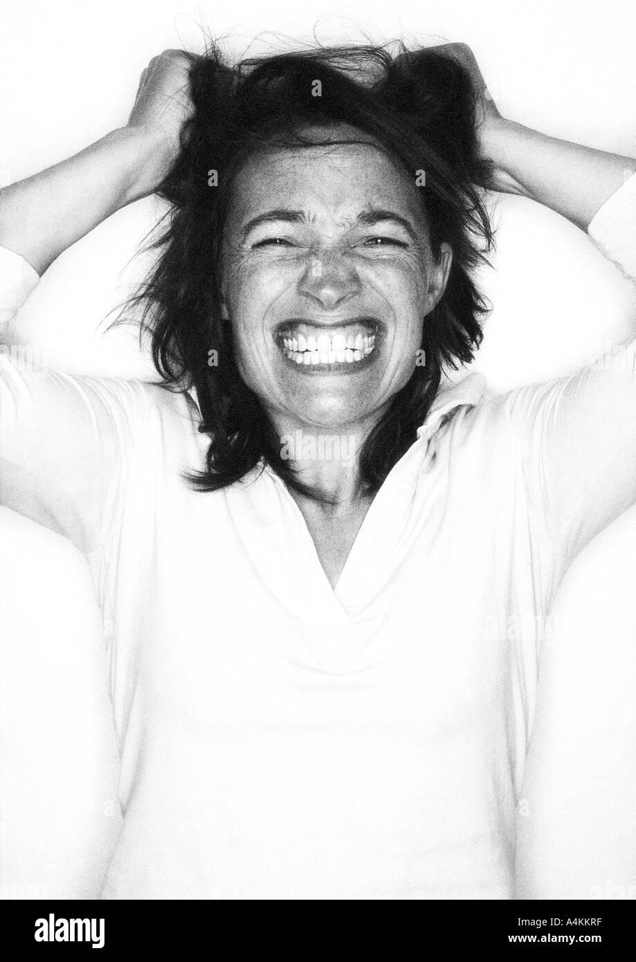 Woman gritting teeth, pulling hair, portrait - Stock Image