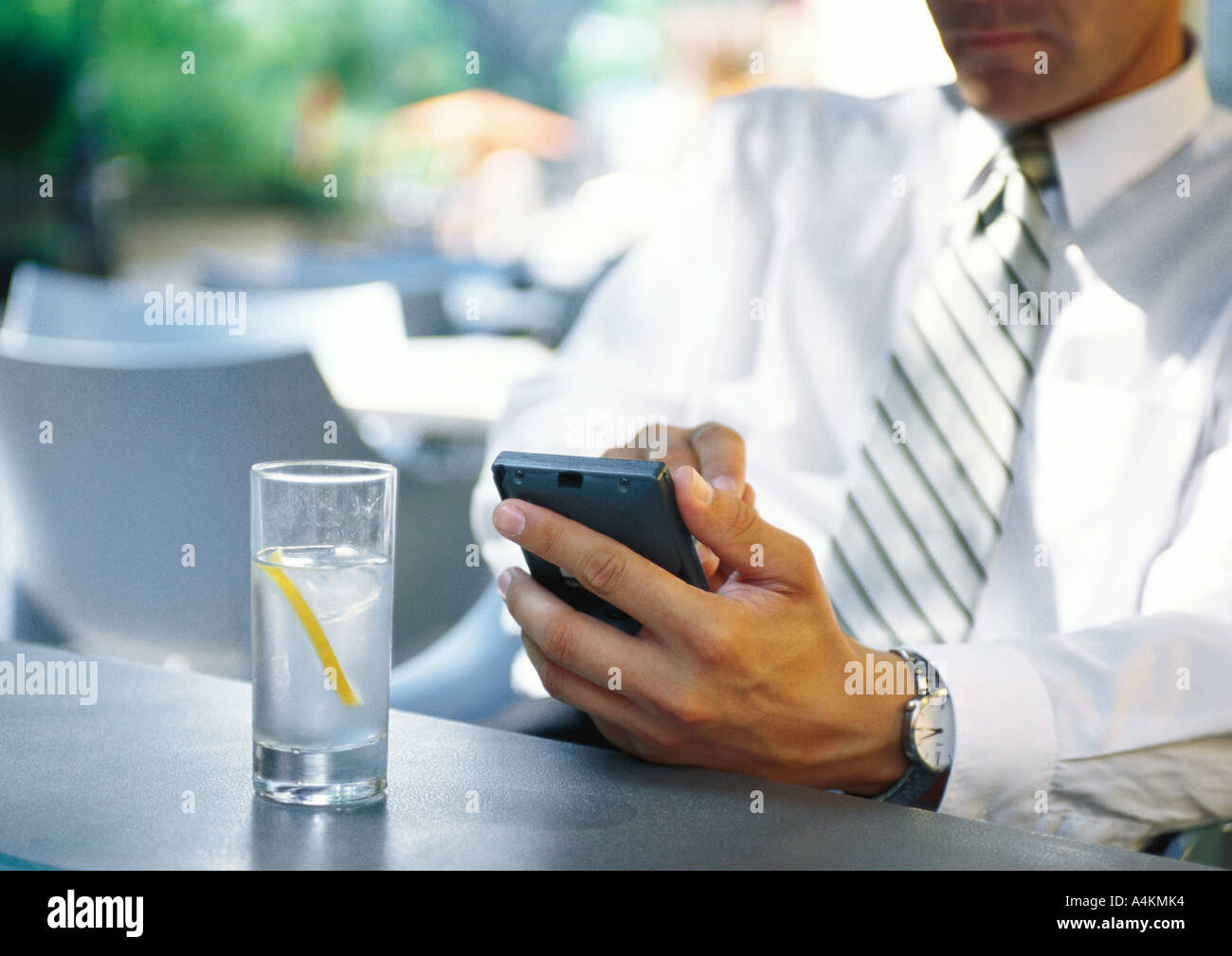 Businesman using electronic organizer in restaurant - Stock Image