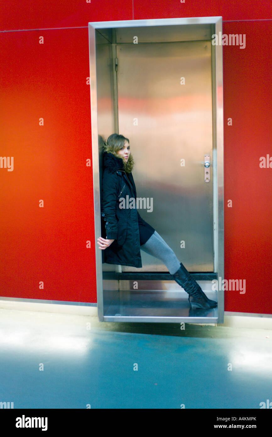 20070115 Switzerland Geneva Young women standing alone at the door - Stock Image