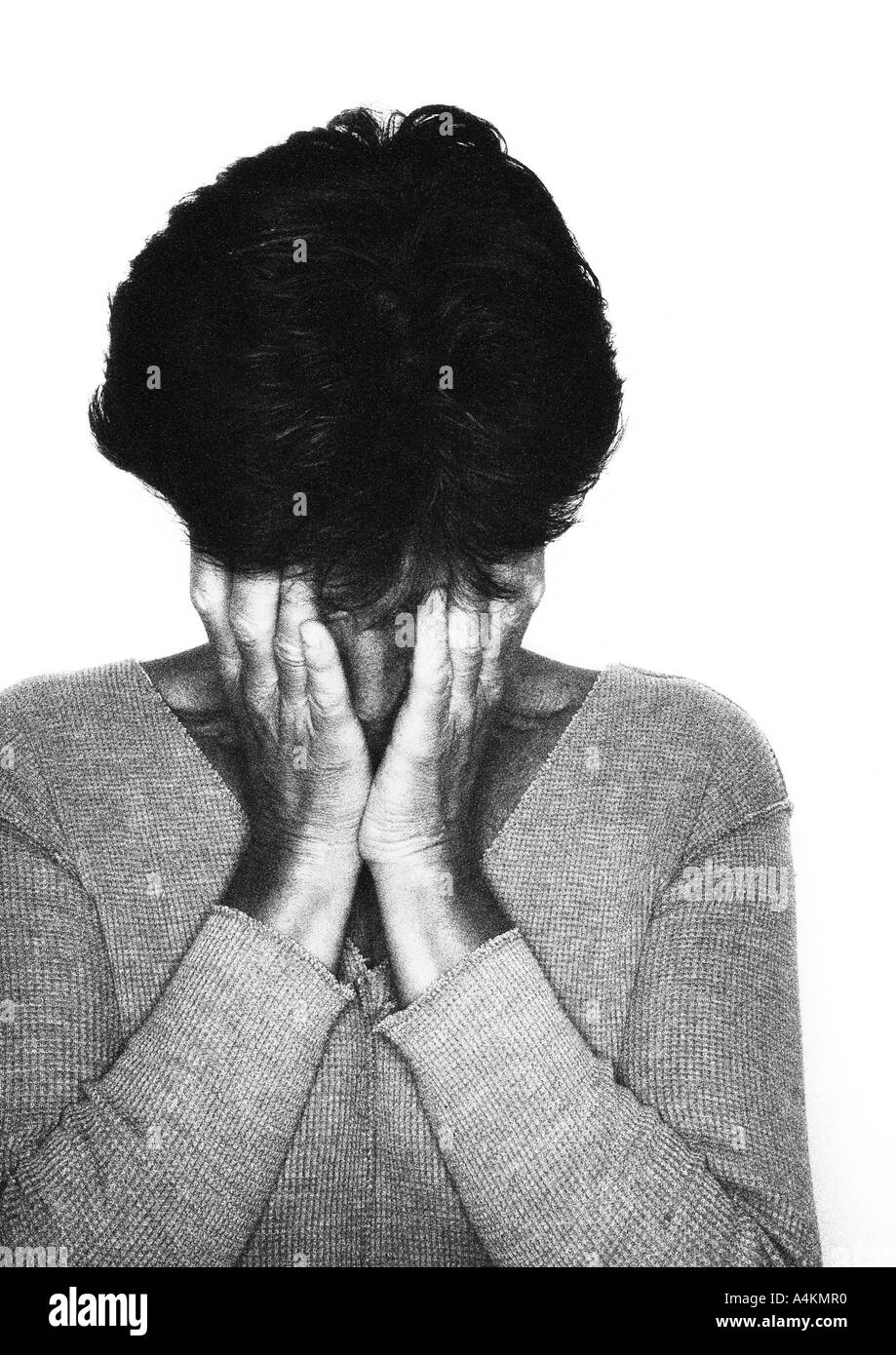 Woman covering her face with hands, portrait, b&w. - Stock Image