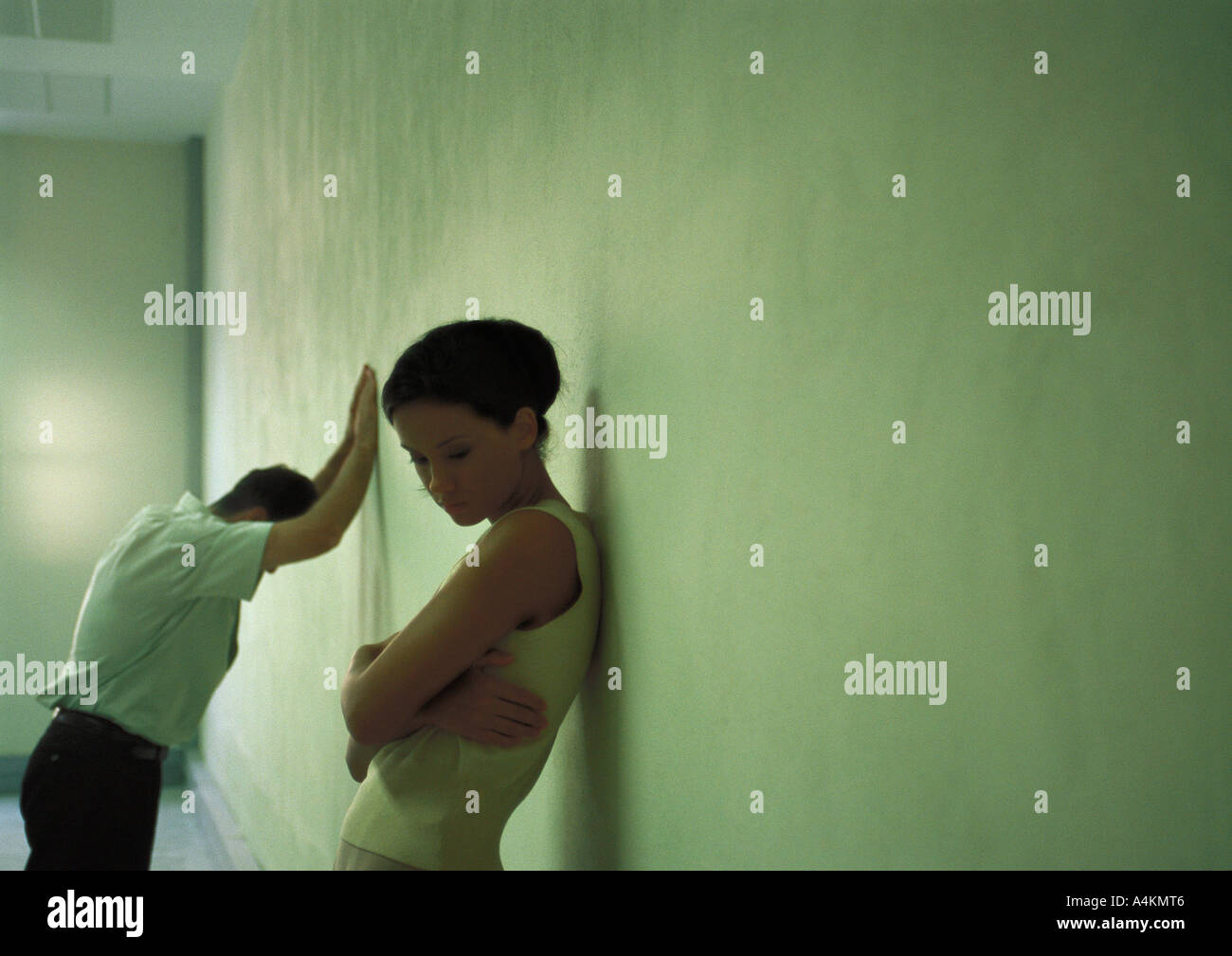 Woman with back against wall, arms folded, man in background leaning despondently against wall - Stock Image