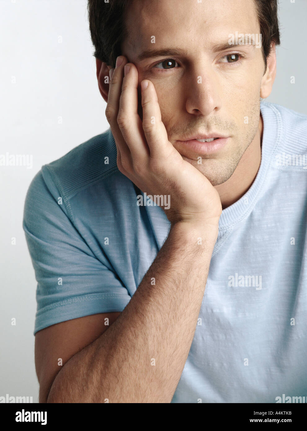 Man Resting Chin On Hand Looking Away Close Up Stock Photo