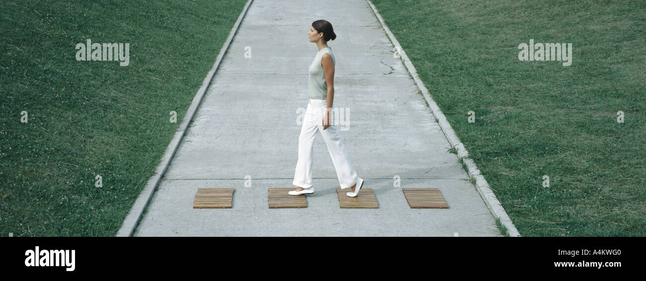 Woman stepping on wood squares across concrete path, full length - Stock Image