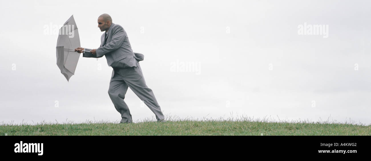 Man walking into wind with open umbrella shielding him, full length - Stock Image