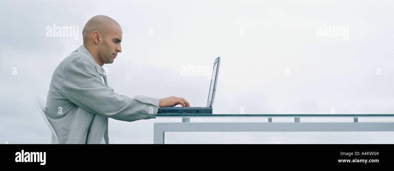 Man sitting outdoors at table using laptop, side view - Stock Image