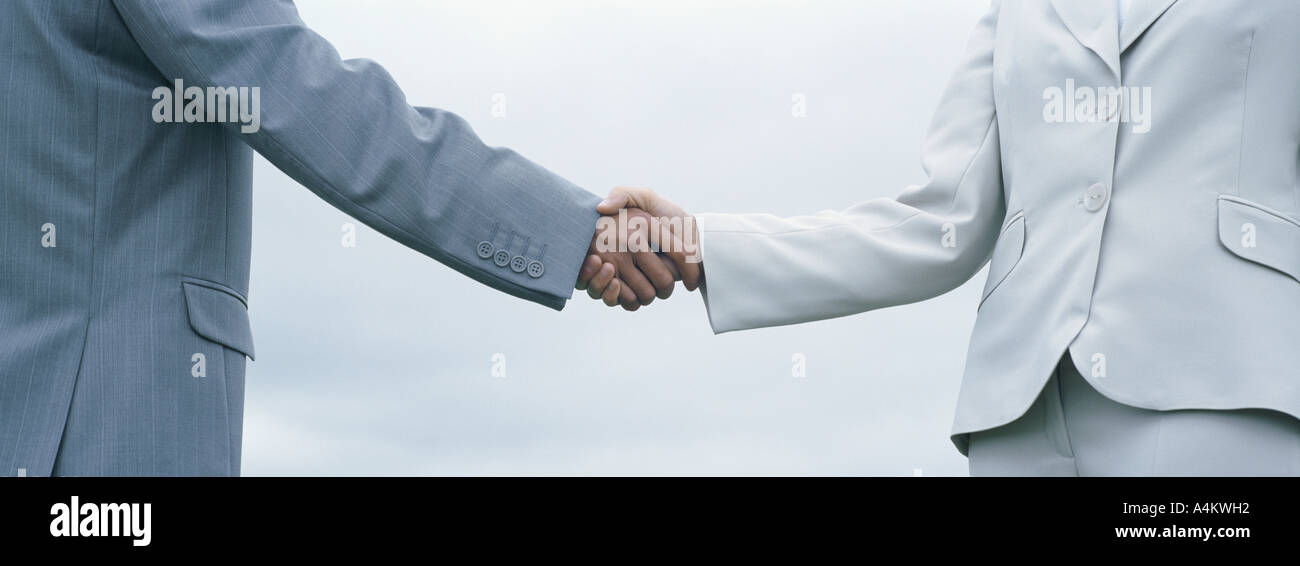 Woman and man in suits shaking hands, mid-section with sky in background - Stock Image