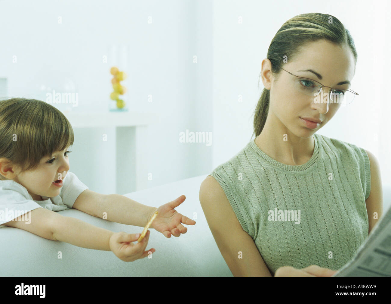 Young woman reading newspaper, ignoring little girl reaching out to her - Stock Image