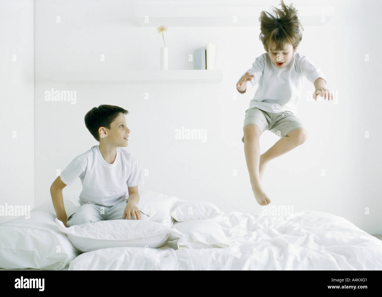 Boys on bed, one in mid air Stock Photo