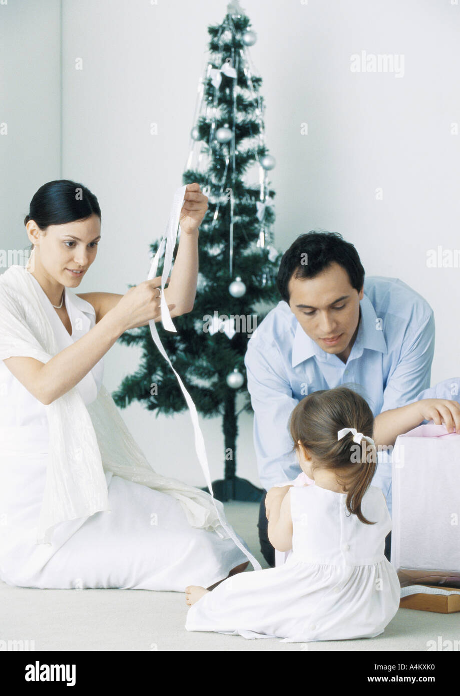 Little girl sitting on floor with parents near Christmas tree Stock Photo