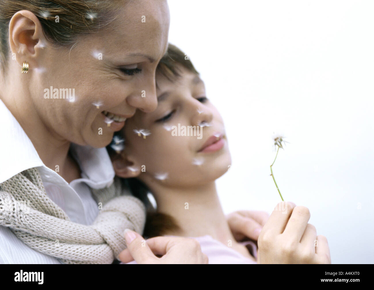 Mother with girl blowing dandelion seeds, close-up - Stock Image