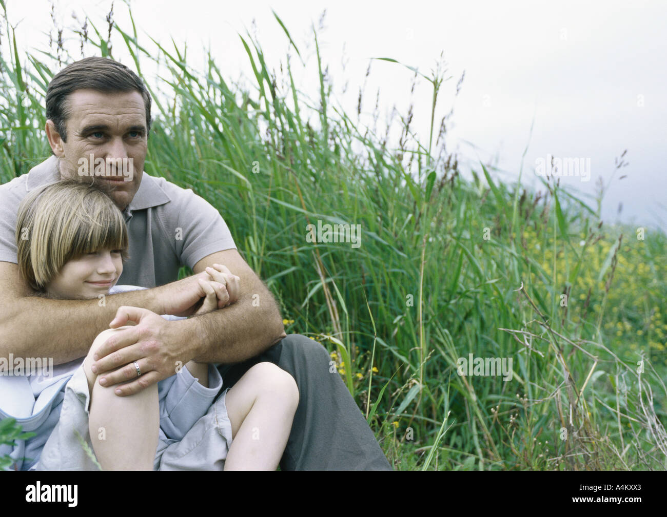 Man sitting on grass with arms around son Stock Photo