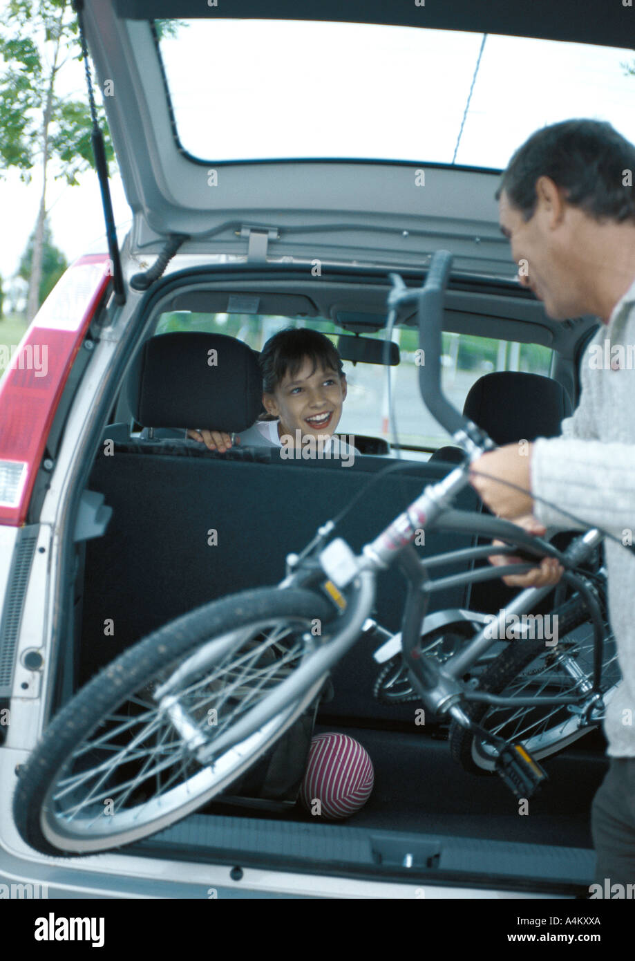 Man putting bicycle into trunk of car, girl in car turning around smiling at man - Stock Image