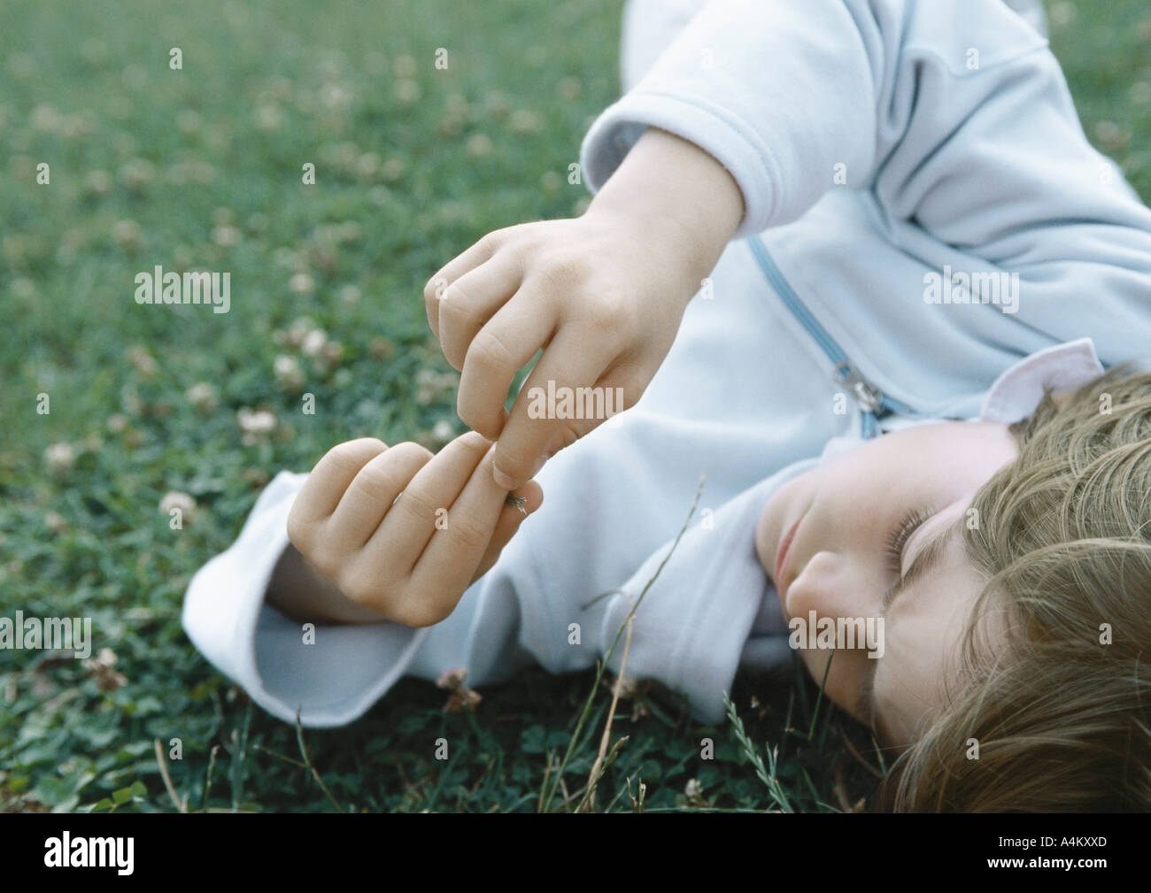 Boy lying on grass holding fingers together in front of face - Stock Image