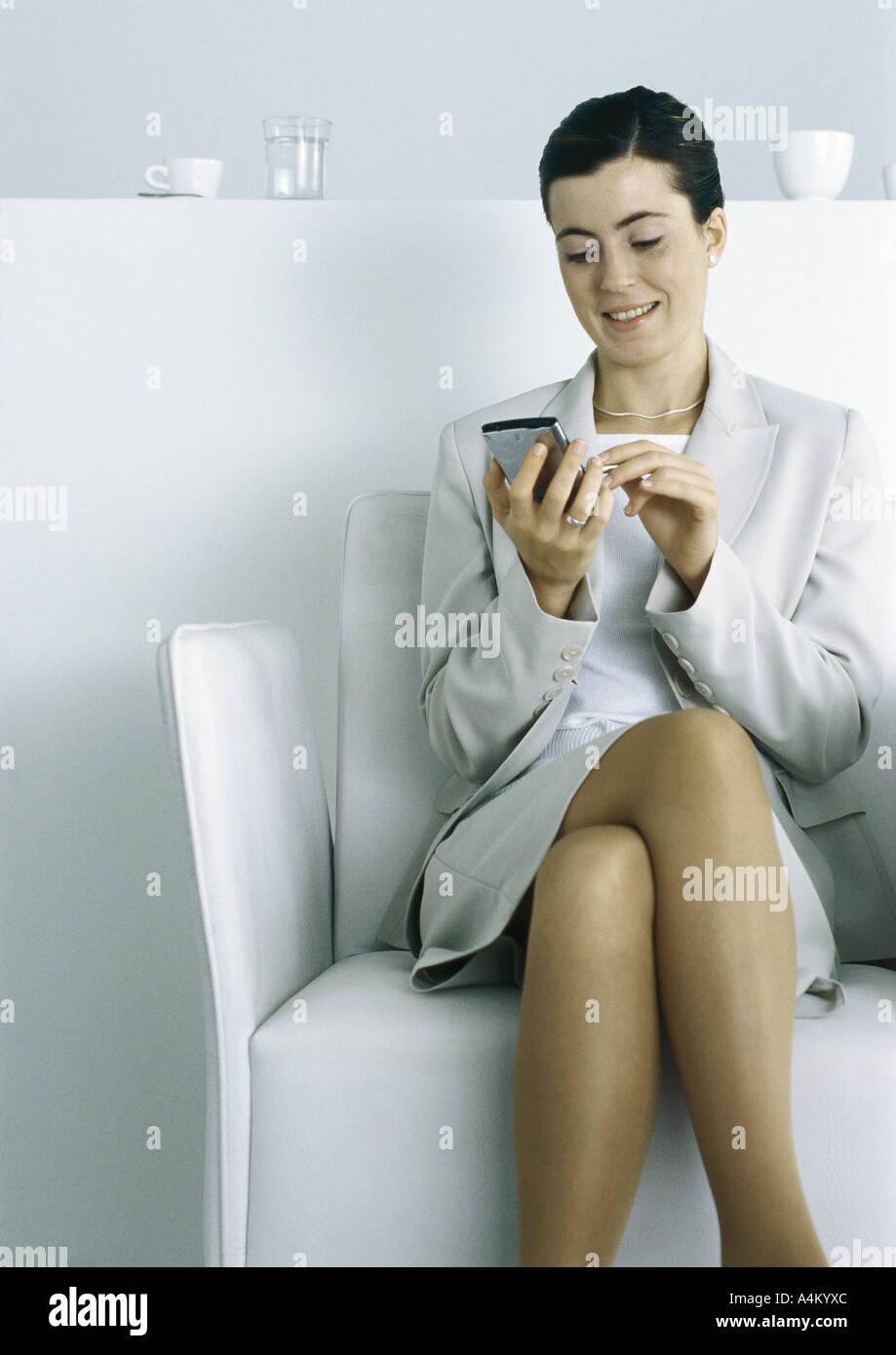 Businesswoman sitting, using electronic organizer - Stock Image