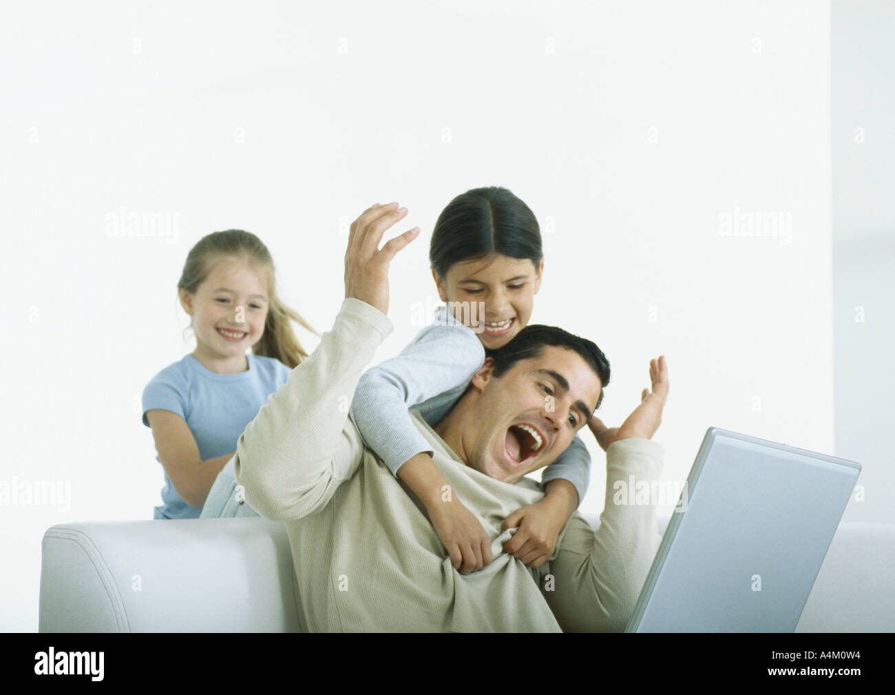 Two girls behind man sitting with laptop, one with arms around him - Stock Image
